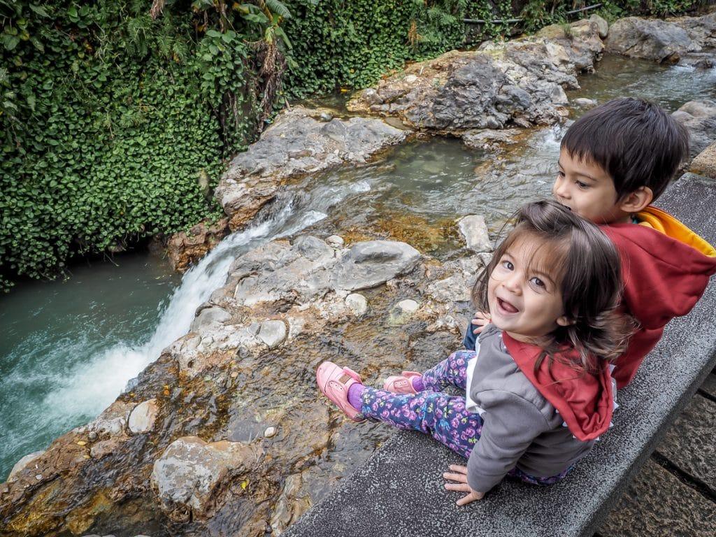 Kids beside hot spring creek in Beitou hot spring park, Taipei