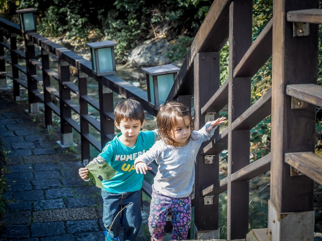 Two kids walking along a hot creek in Beitou, one of the best things to do in Taipei in December