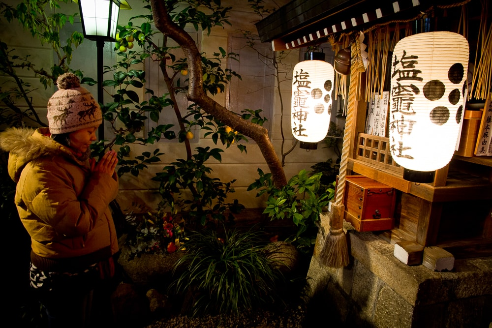 Praying at a small temple in the Teramachi Shopping Arcade, Kyoto