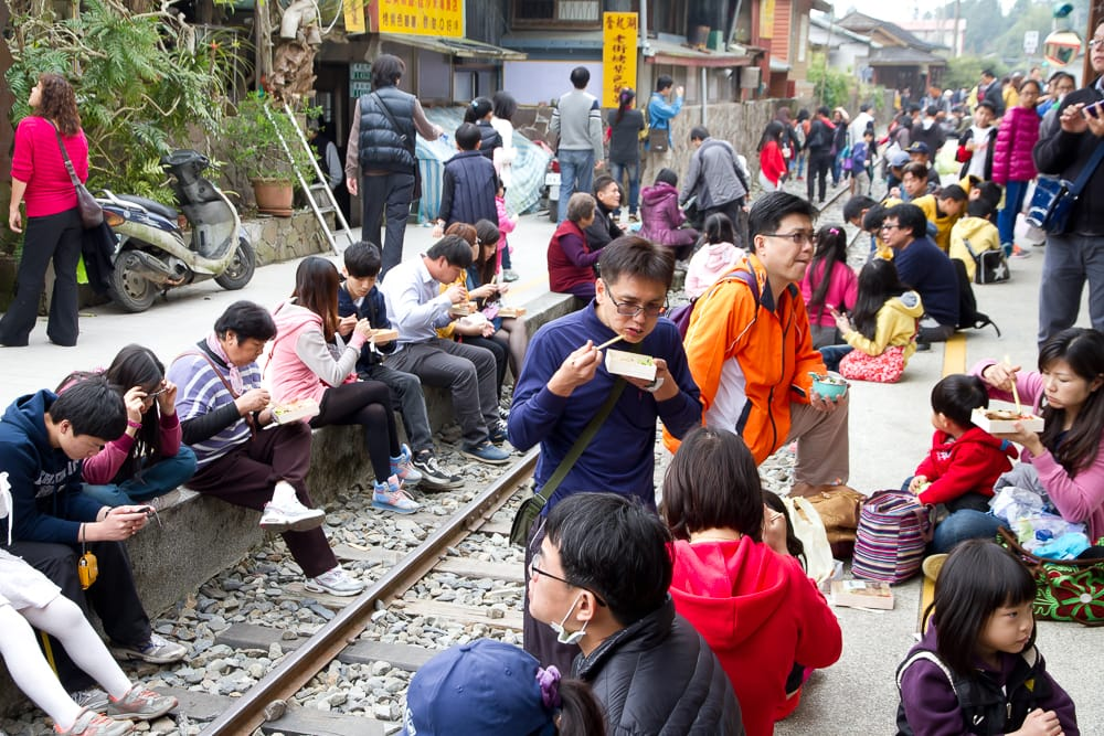 Taiwanese people eating Fenqihu lunchboxes on the train tracks at Fenqihu station