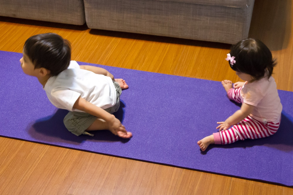 my toddler son showing off his yoga moves to my baby daughter