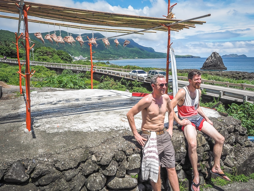 Two travelers and some flying fish hanging to dry during the Orchid Island flying fish festival.