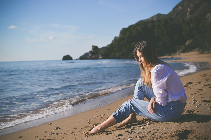 A woman sitting and contemplating the present moment on the beach
