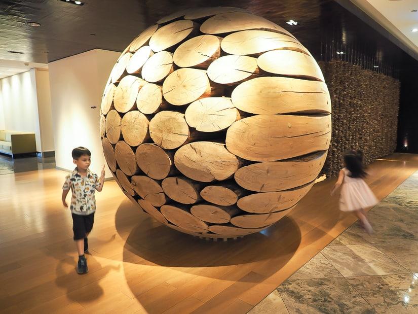 Our kids running around a large artwork in the lobby of Grand Hyatt Taipei