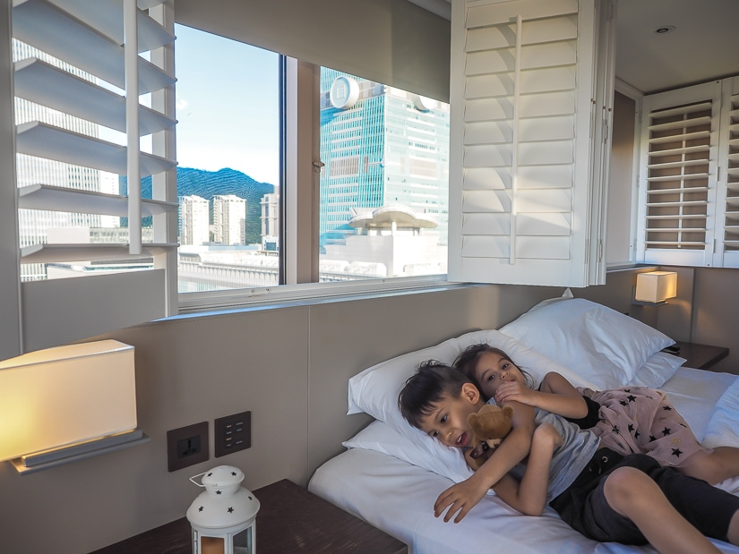 Our kids and view of Taipei 101 from king sized bed in our suite ant Grand Hyatt Taipei