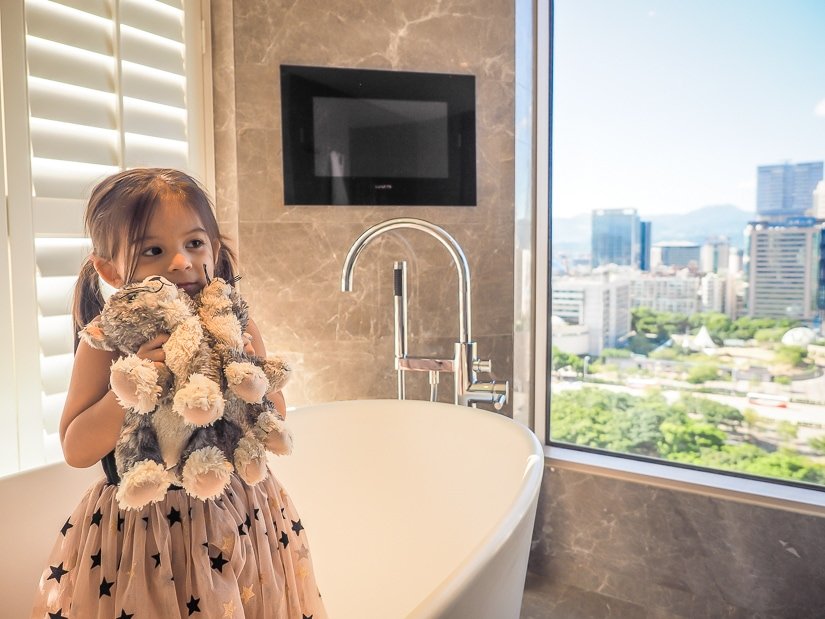 My daughter in bathroom with teddy cat in our Grand Hyatt Executive Suite