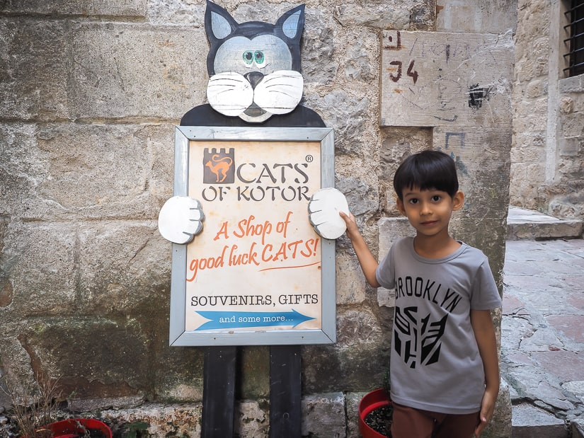 My son standing by the sign of the Cats of Kotor shop