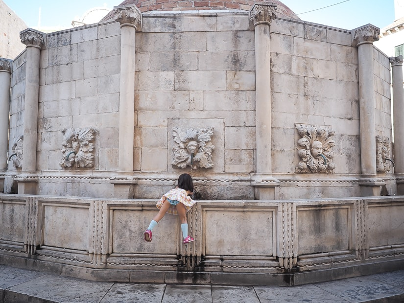 My daughter reaching in to the Jewish Fountain in Dubrovnik