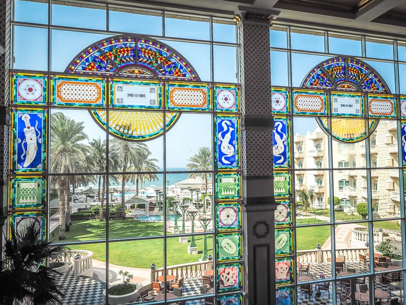 Large stained glass windows at the front end of the Grand Hyatt Muscat lobby