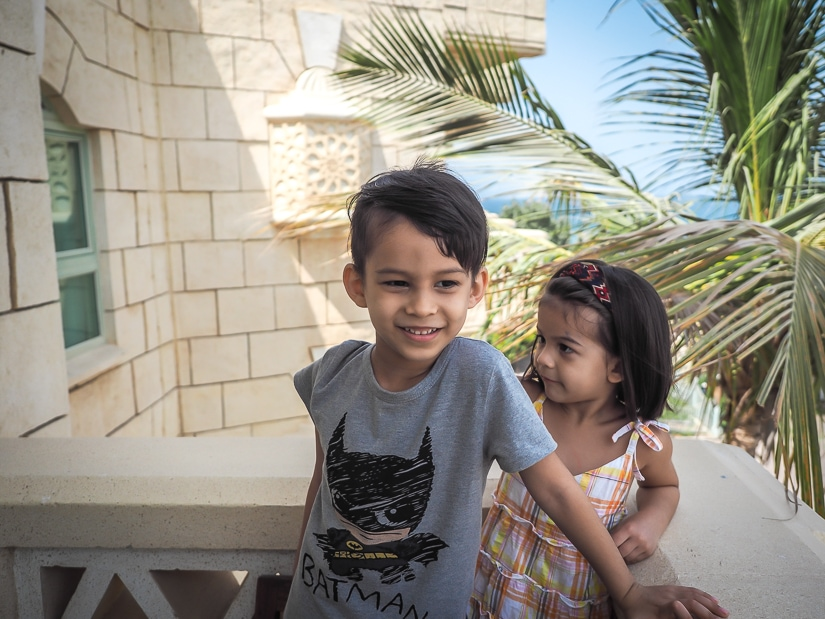 Our kids on the balcony of our Grand Hyatt king suite, with the sea in the background