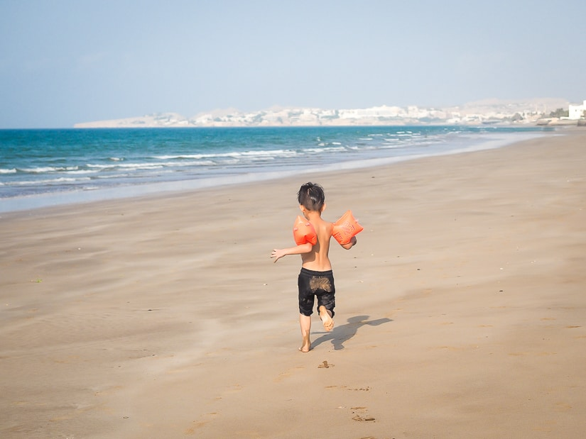 My son running on the beach in front of the Grand Hyatt