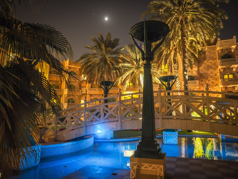 Grand Hyatt Muscat swimming pool and palm trees at night