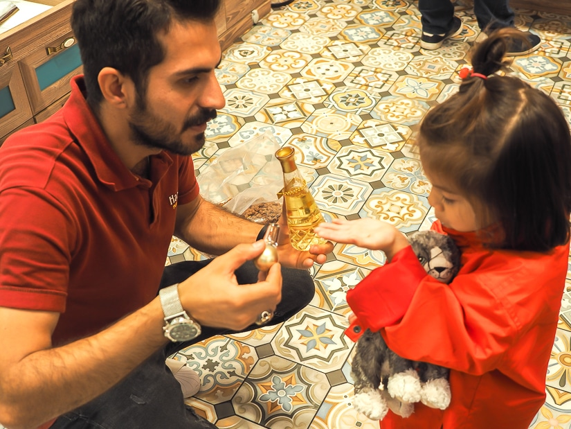 A spice market vendor putting some perfume on my daughter's wrist