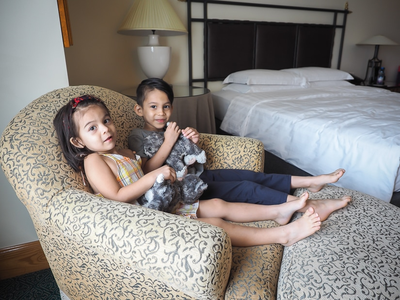 Our kids sitting in a love seat in our Grand Hyatt suite