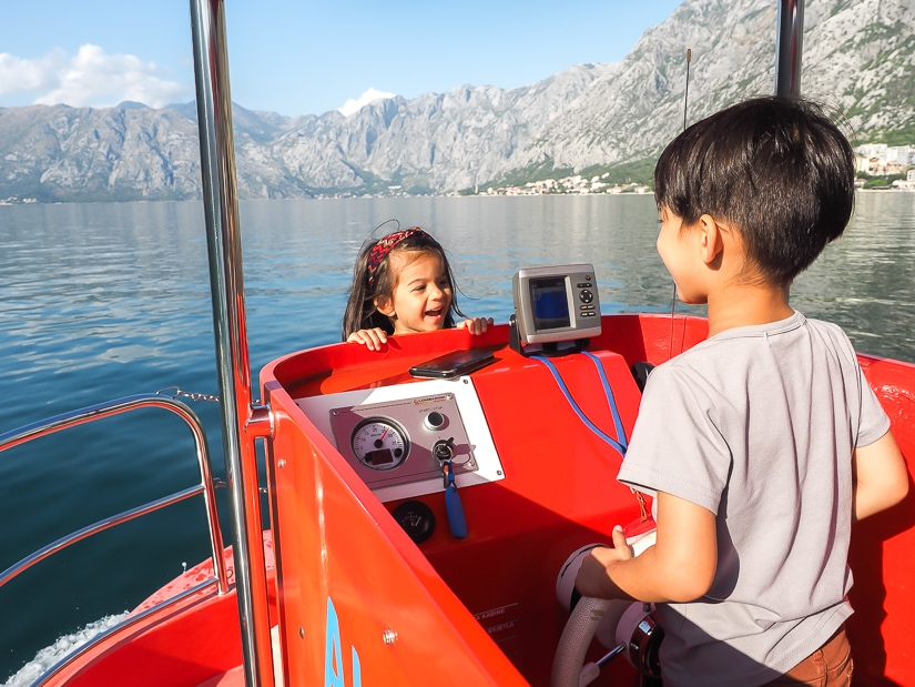 My son driving a boat on the Bay of Kotor, with my daughter facing him