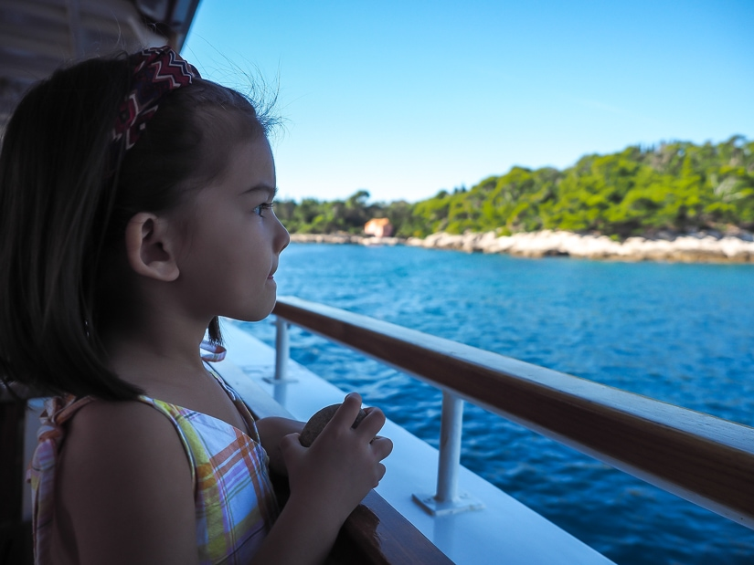 Child on ferry with shore of Lokrum Island in background
