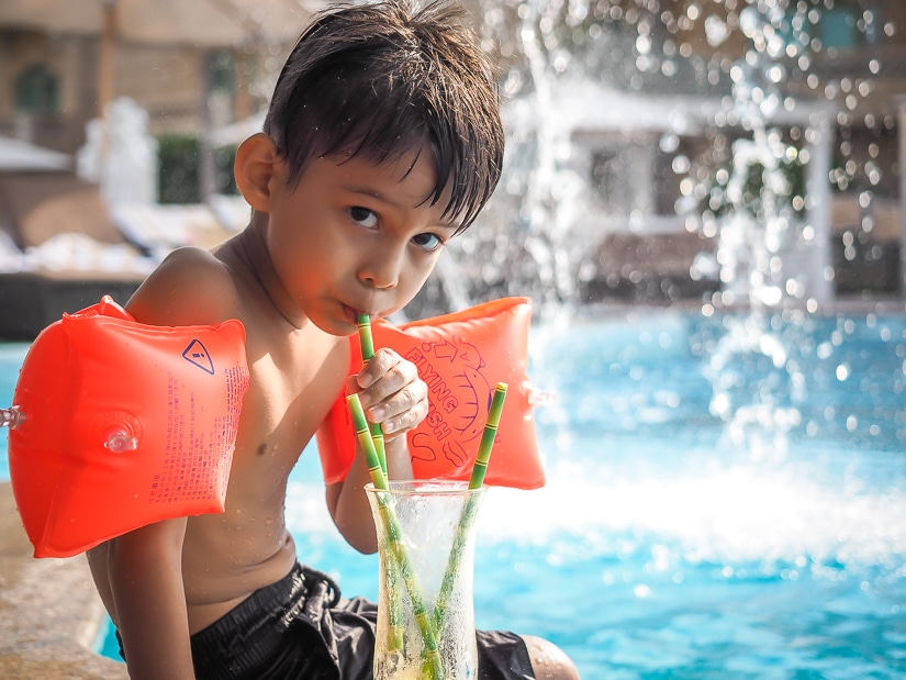 My son Sage having a mango smoothie at the Grand Hyatt Muscat poolside
