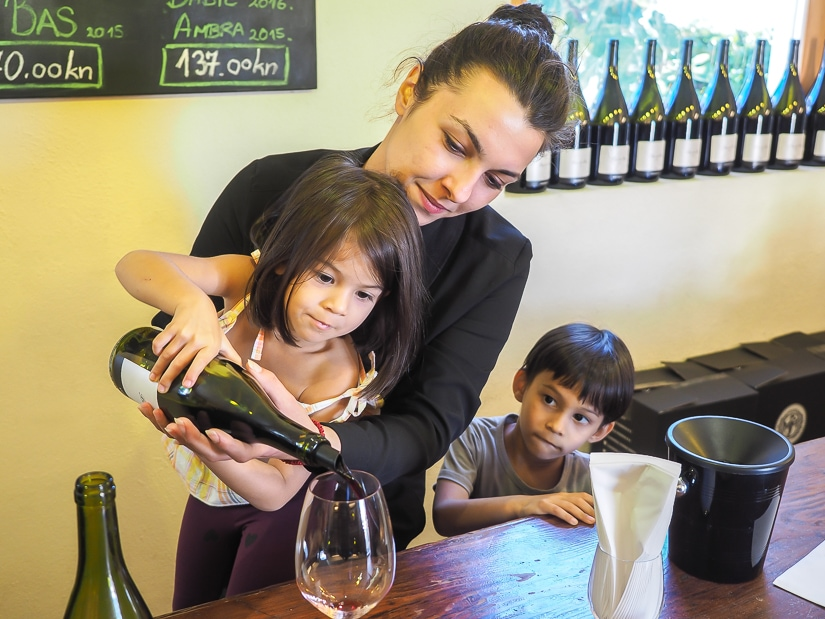 A woman helping our kids to pour wine at Bibich winery near Skradin in Croatia