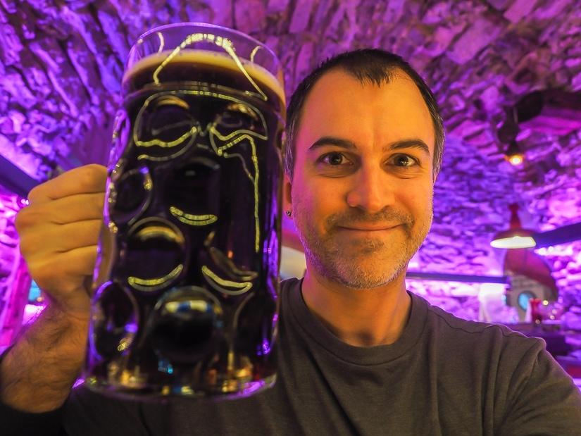 Me holding a large glass of dark beer at Braukeller restaurant in Seefeld