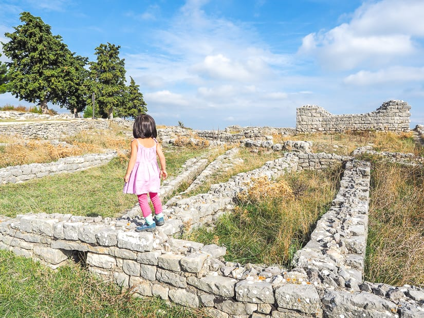 My daughter overlooking some ancient ruins, which we were able to visit by renting a car for our Croatia family trip