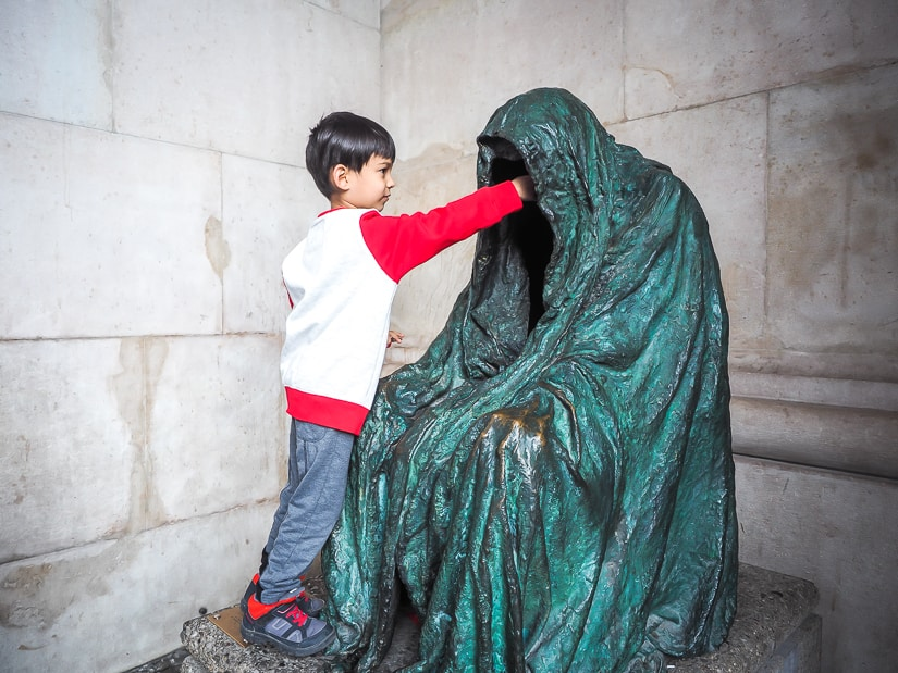 My son reaching into a hallow statue on Kapitelplatz Square in Salzburg