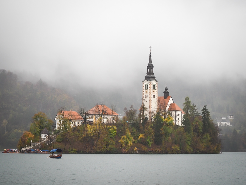 Lake Bled in October and November: Bled Island with lots of gray clouds over it