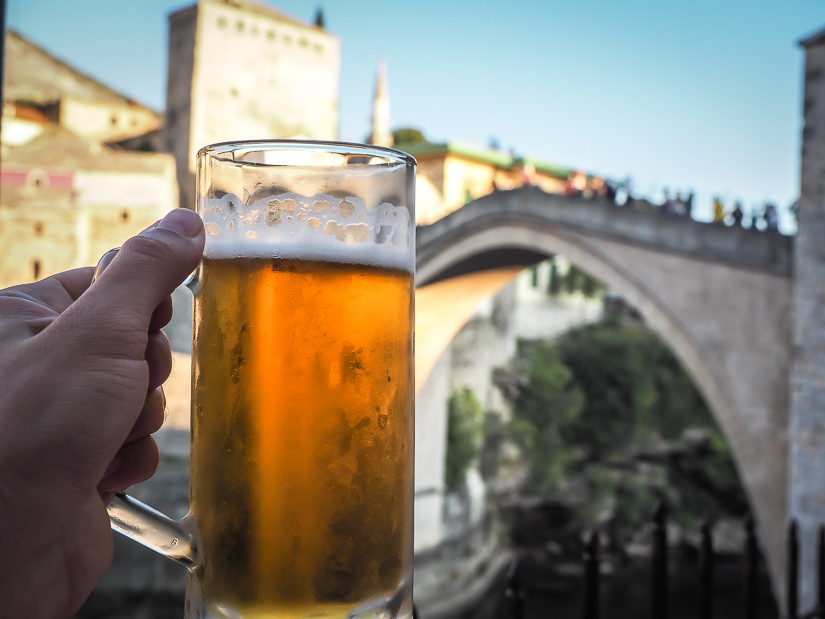 A large beer with Mostar Bridge in the background
