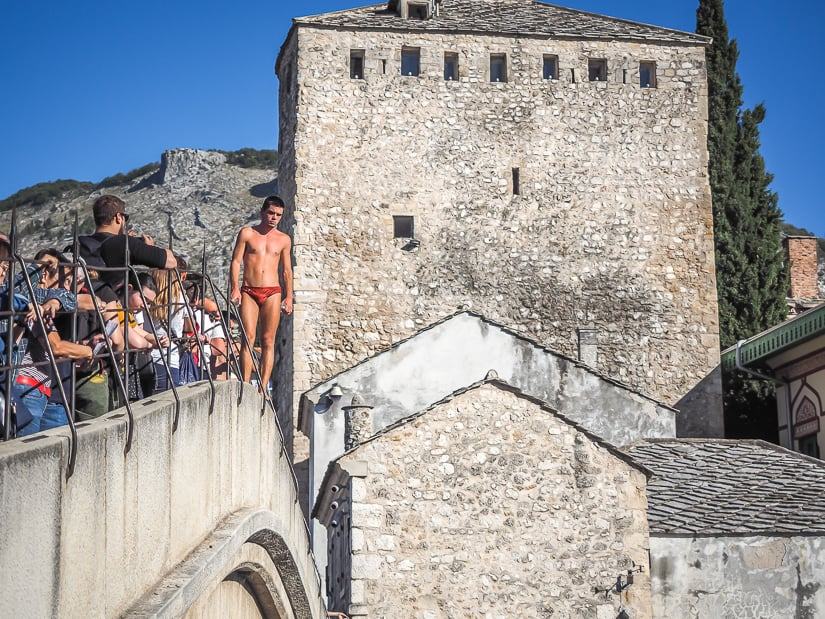 A Mostar bridge diver standing on Stari Most and waiting for donations to jump