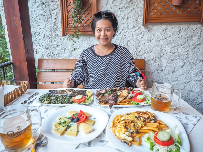 My wife with several plates of food in front of her in a restaurant in Mostar