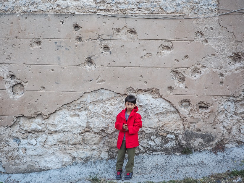 My son in front of a wall damaged by gunshots in Mostar
