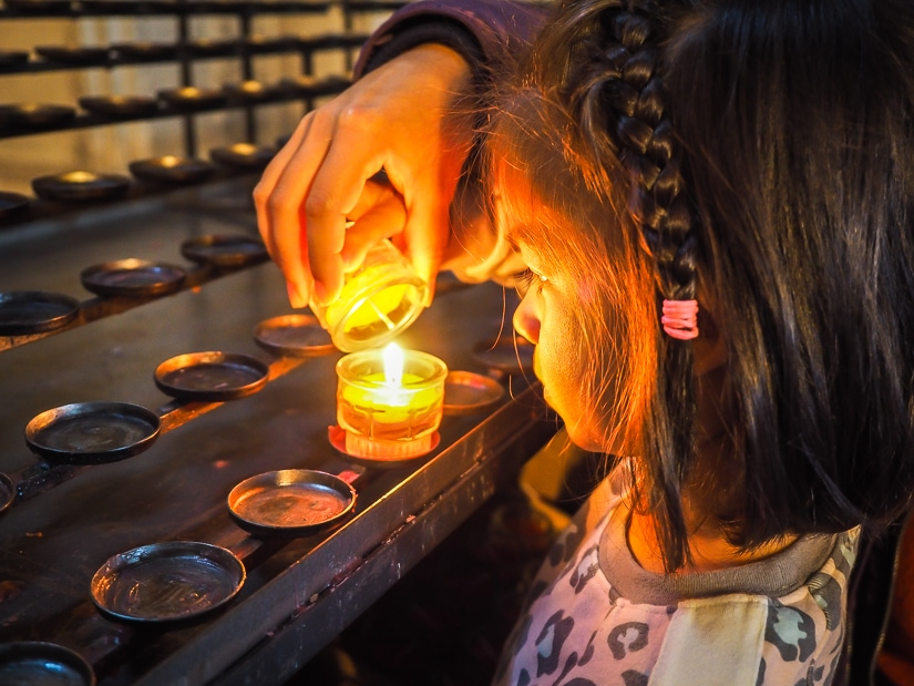 My daughter lighting a candle when we visited Salzburg Cathedral with kids