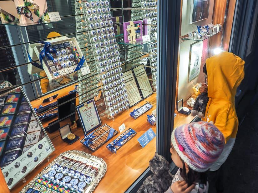 Our kids looking at Mozart chocolate balls through the window of Confiserie Fürst, a shop in Salzburg