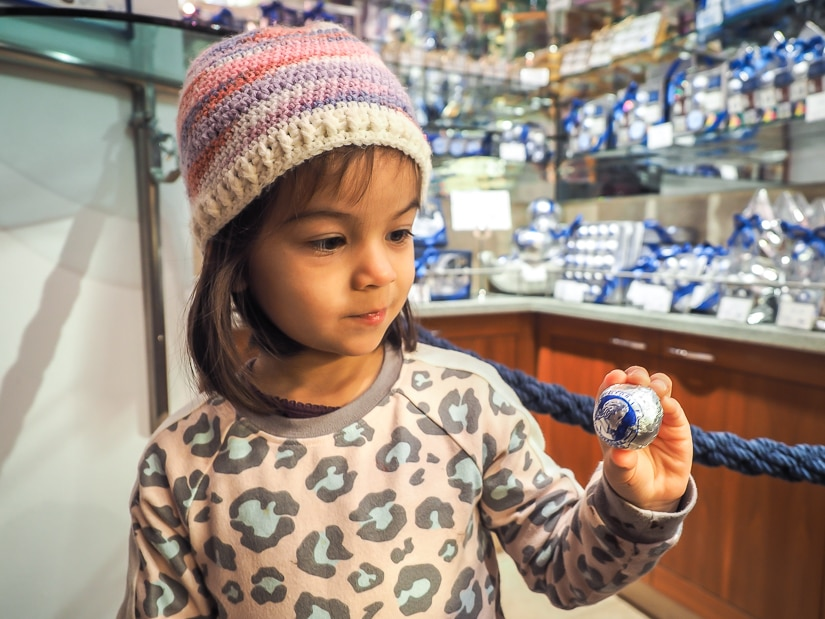 My daughter holding up a Mozart chocolate ball in Confiserie Fürst, a chocolate shop in Salzburg, one of the best places to visit in Austria with kids