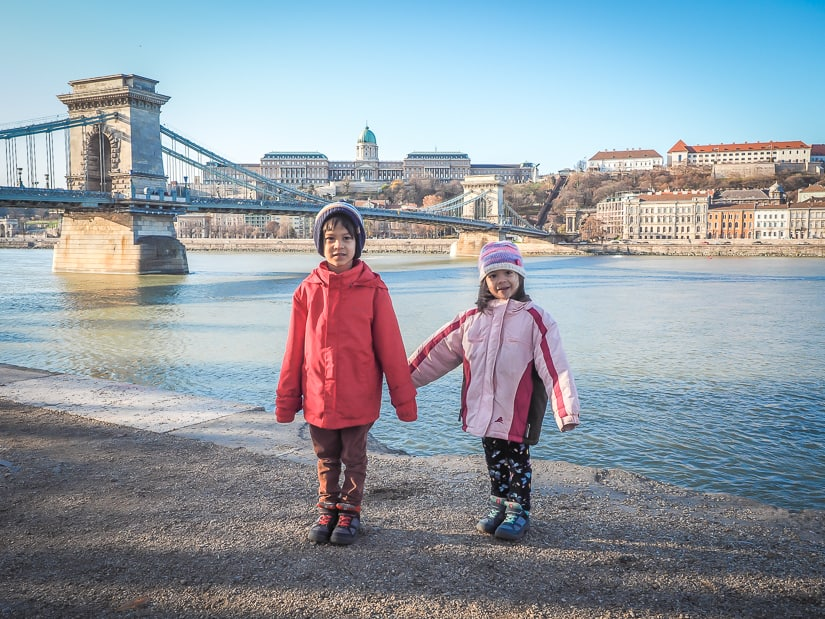 Our kids beside the Danube river in Budapest, with Széchenyi Chain Bridge and Buda Castle in the background