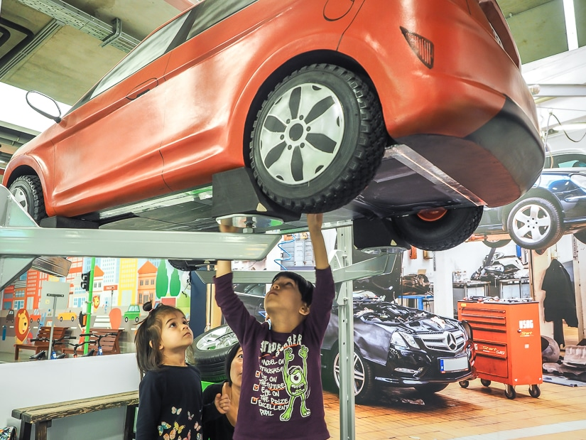 Our kids pretending to repair under a car at MiniPolisz, Budapest