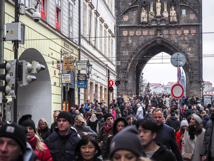 Crowds of people at the entrance of Charles Bridge in Prague