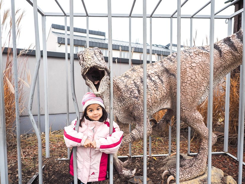 My daughter inside a cage with a fake velociraptor at Dino Park Prague