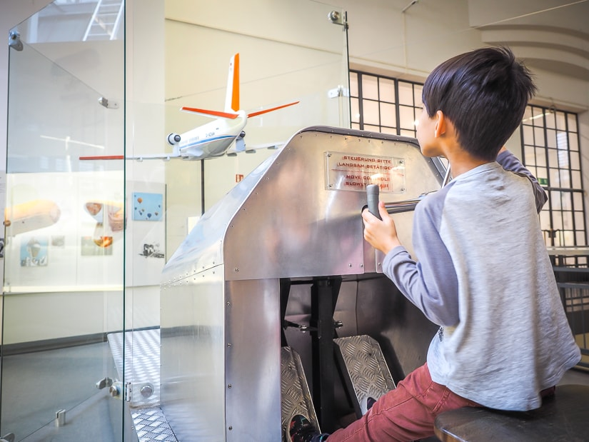 My son practicing flying an airplane at the Deutsches Museum, one of the best places to visit in Munich with kids