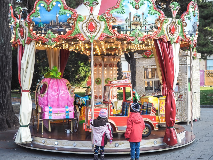 Our kids beside a merry-go-round (carousel) at Karlsplatz Christmas Market, perhaps the most family-friendly Christmas market in Vienna