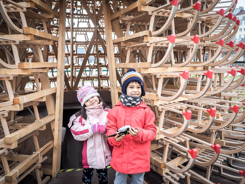 Our kids in front of a Christmas tree made of wooden sleds. Read on to find out the best places to visit in Vienna in winter with kids!