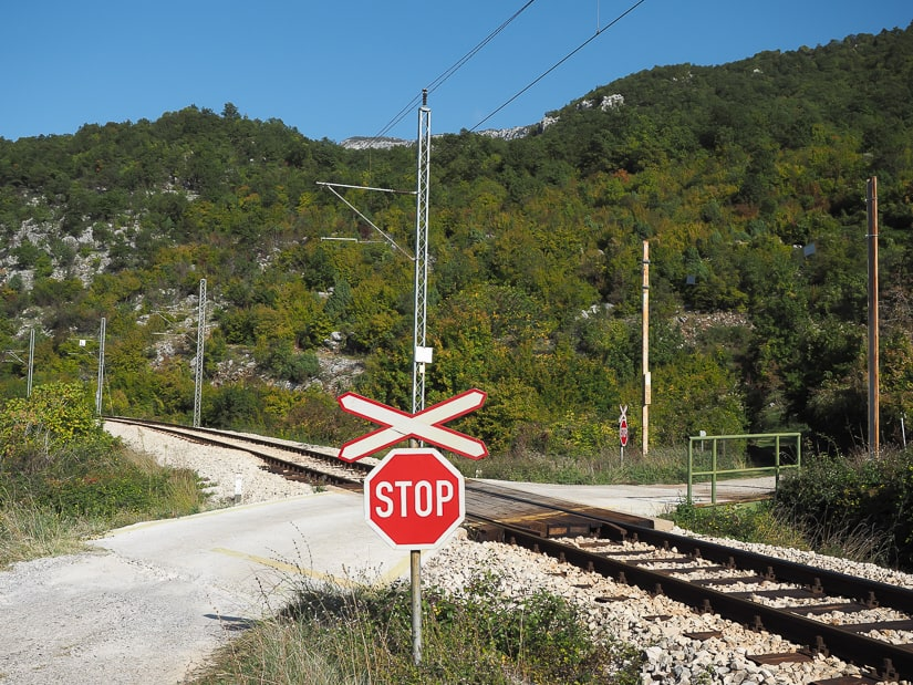 Stop sign that indicates where to cross the train tracks to find the entrance to the walking trail to Ostrog Monastery