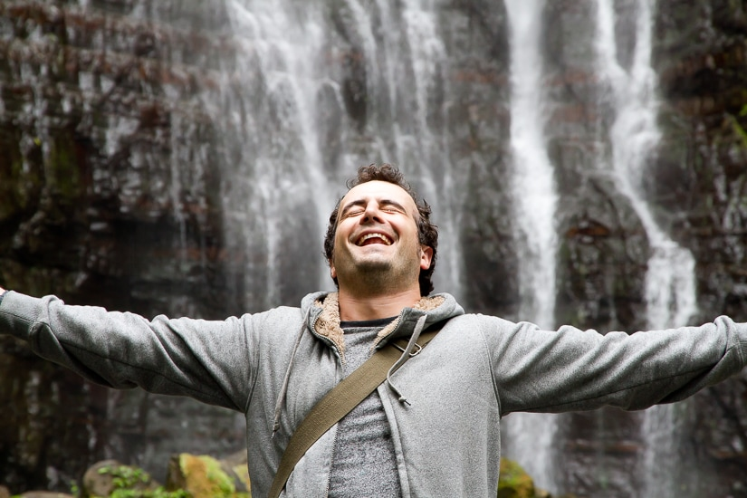 Man standing with arms open in front of Wufengqi Waterfall in Jiaoxi, Yilan