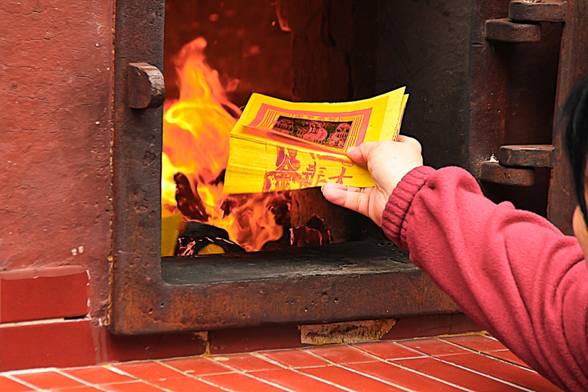 A hand putting some ghost money into a fire, part of the rituals that take place during Ghost Month in September in Taipei