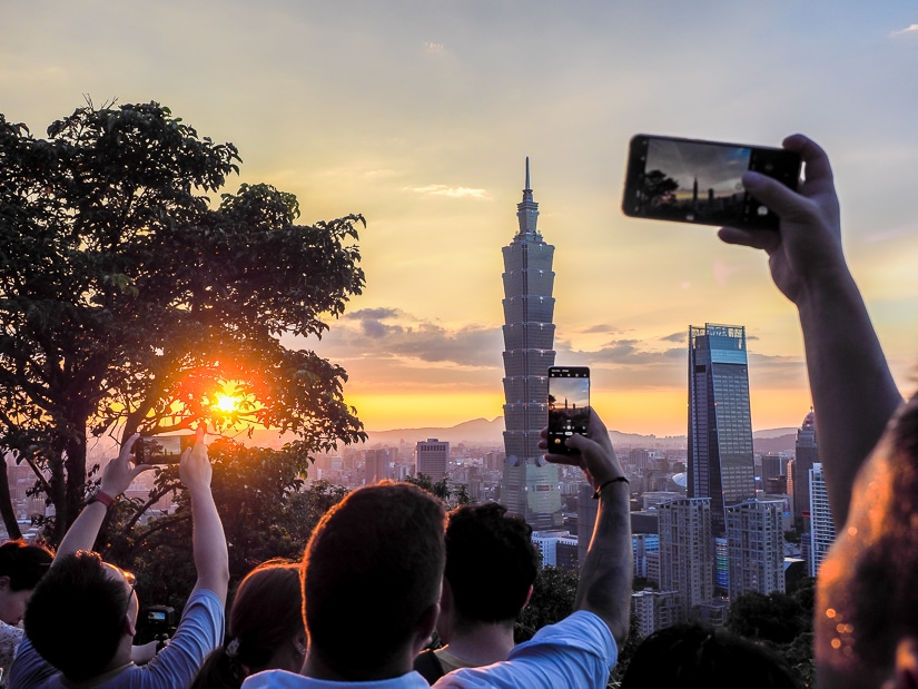 Tourists photographing Taipei 101 from Elephant Mountain in Taipei in summer