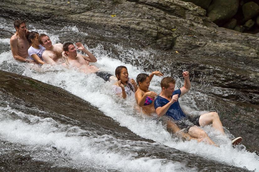 A group of people sliding down a rock slide on Jiajiuliao Stream river tracing run, Wulai