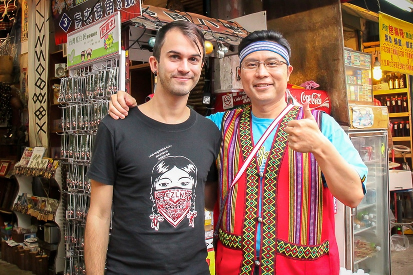 Me standing with a Taiwanese vendor on Wulai Old Street who is dressed like an aboriginal but not really one.