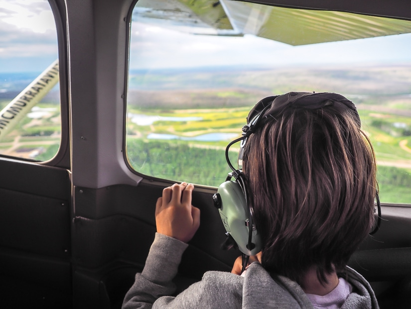A young girl looking out the window as our aerial tour in Fort McMurray takes off