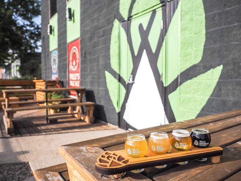 Flight of beers on picnic table in the outdoor patio at Hell's Basement, the best brewery in Medicine Hat