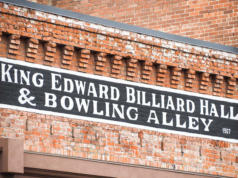 Original sign on a brick store front of King Edward Billiard Hall & Bowling Alley, dating to 1907.
