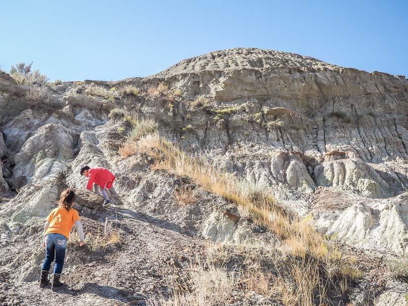 Two kids climbing dry, arid hills